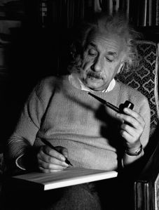 Albert Einstein smokes a pipe and writes as he sits working in a comfortable chair in his study.